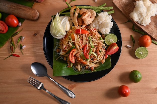 Green papaya salad with sticky rice on wooden table. thai traditional food.