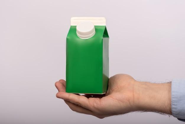 白の男の手で緑の紙袋。ジュースヨーグルトミルクパッケージ。モックアップ。