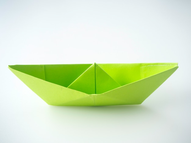 Green paper boat laid on white background.
