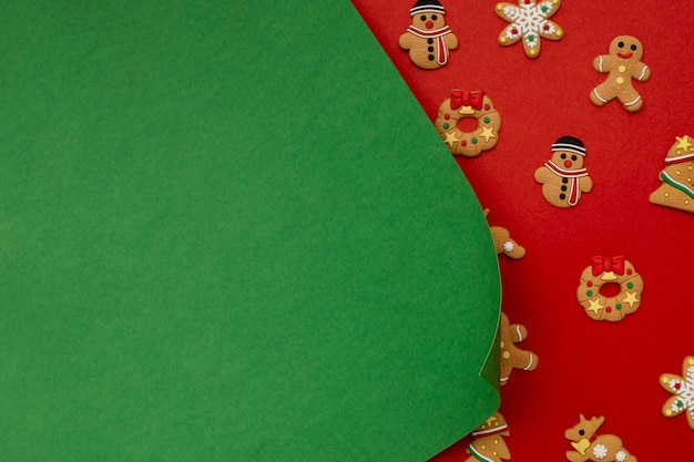 Green paper and christmas cookies on red table
