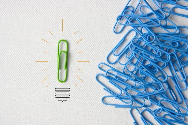 Зеленая скрепка, округленная лампочкой рядом с большим количеством синей скрепки