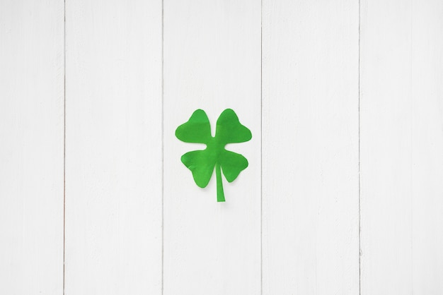 Green paper clover on board