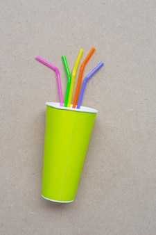 Green paper coffee cup with straws  on plywood