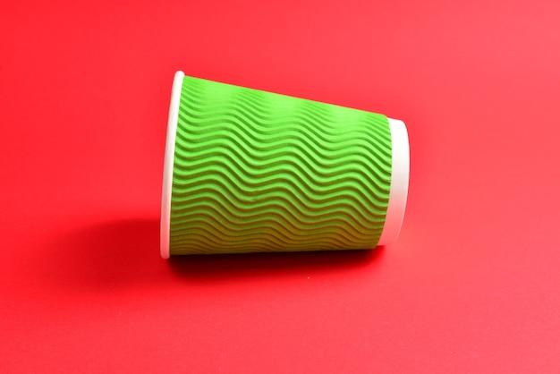 赤の背景に緑の紙コップ。スペースをコピーします。