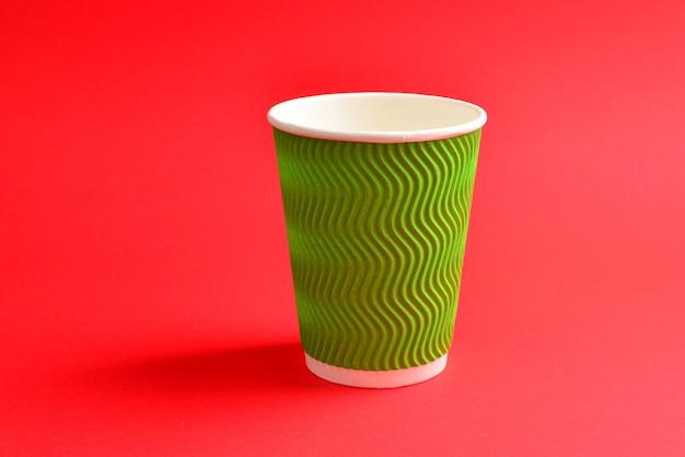 Зеленый бумажный стаканчик на красной стене