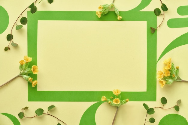 Green paper frame decorated with yellow primrose flowers and leaves, flat lay on yellow paper