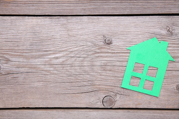 Green paper house on a grey wooden background