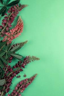 꽃 루핀으로 만든 장식이 있는 텍스트용 녹색 종이 모형