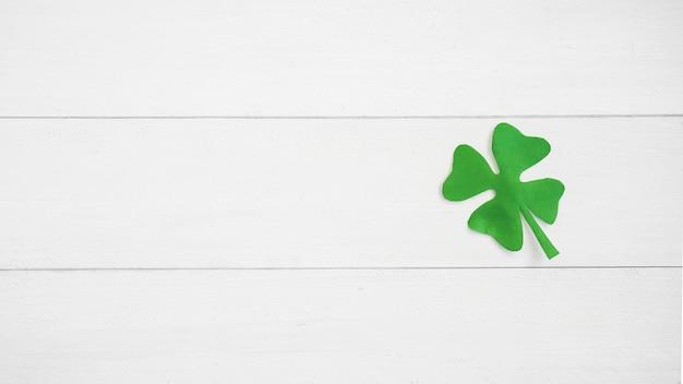 Green paper shamrock on board