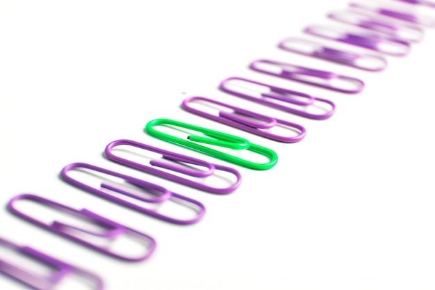Зеленая скрепка и множество фиолетовых скрепок уникальная концепция