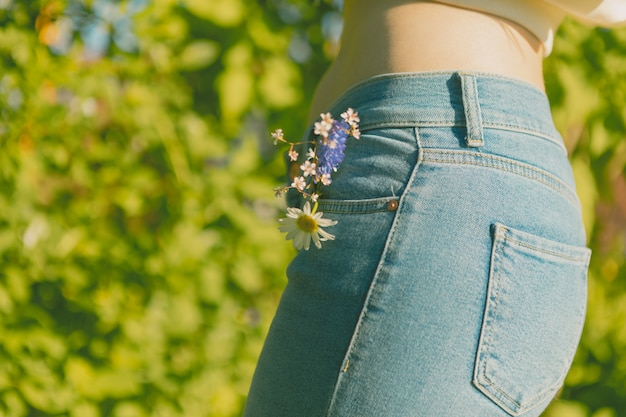 Green park and a slender girl in blue jeans with wildflowers in her pocket.
