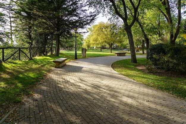 햇빛과 벤치에 앉아 포장 된 경로와 녹색 공원. 부르고스,