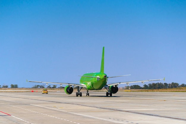 Green passenger airplane at the airport on sunny day