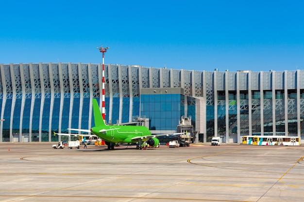 晴れた日の空港での緑の旅客機