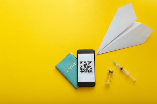 스마트폰 화면의 녹색 여권 코로나바이러스 qr 코드, 백신 주사기 covid 19, 종이 비행기. 디지털 인증서 코로나 백신 통과. 노란색에 복사 공간이 있는 무료 해외 여행