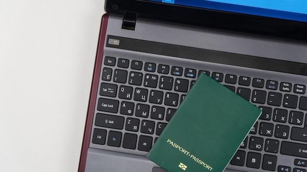 Green passport on the laptop keyboard. online registration. top view