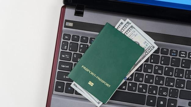 ノートパソコンのキーボードに米ドルが記載されたグリーンパスポートオンライン登録賄賂と汚職
