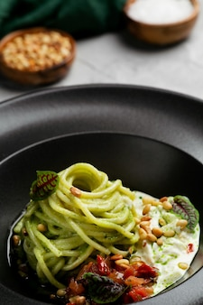 페스토 소스, 토마토, 바질을 곁들인 그린 파스타 스파게티. 시금치 야채와 견과류가 들어간 파스타
