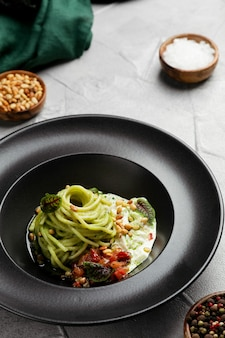 Green pasta spaghetti with pesto sauce, tomatoes and basil. pasta with spinach vegetables and nuts