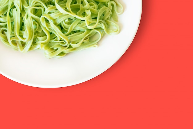 Green pasta on a white plate isolated on a living coral