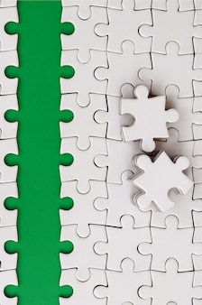 The green path is laid on the platform of a white folded jigsaw puzzle.