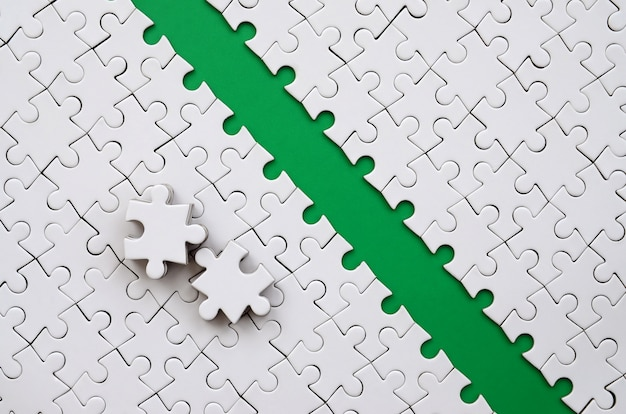 The green path is laid on the platform of a white folded jigsaw puzzle