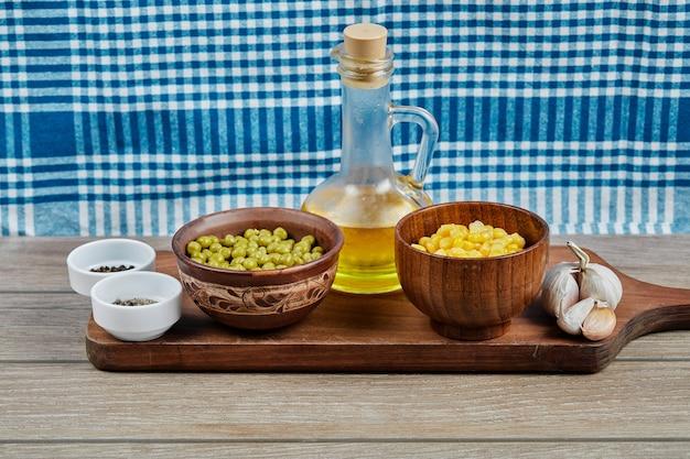 Зеленый горошек и кукурузные бобы в деревянных чашках.