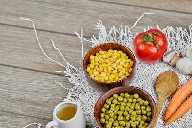 Fagioli e semi di pisello verdi in tazze di legno.