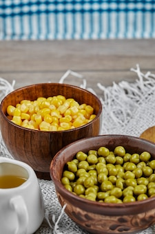 Piselli verdi e fagioli di mais in tazze di legno.