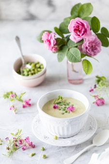 Green pea cream soup on a white marble table with a bouquet of roses