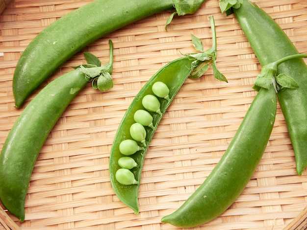 Green pea pod in a bamboo container