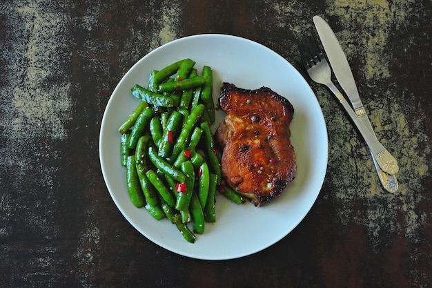 Green pea pods and pork steak on a plate. keto diet.