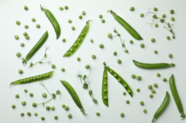 緑のエンドウ豆の鞘、白い背景の上の種子や小枝