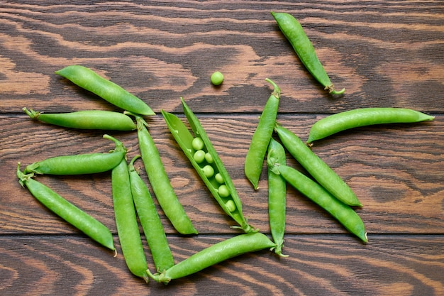Green pea pods on wooden table, top view
