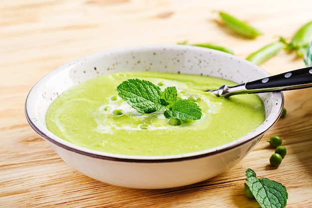Green pea soup in bowl on wooden table, french cuisine.