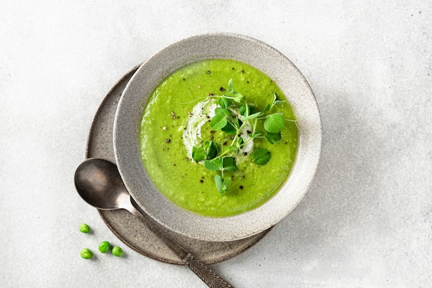 Green pea soup in a ceramic bowl on gray concrete background top view