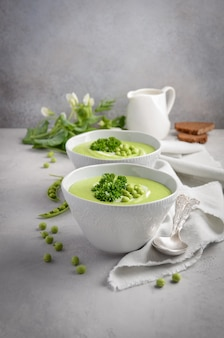 Green pea soup on gray concrete or stone background.