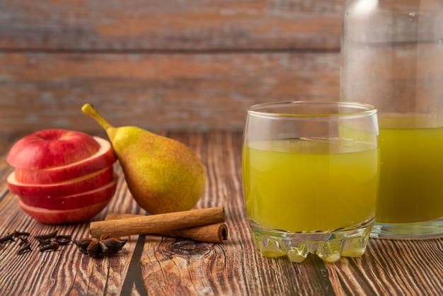 Зеленая груша и красное яблоко со стаканом сока