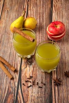 緑色の洋ナシとジュースのガラスと赤いリンゴ