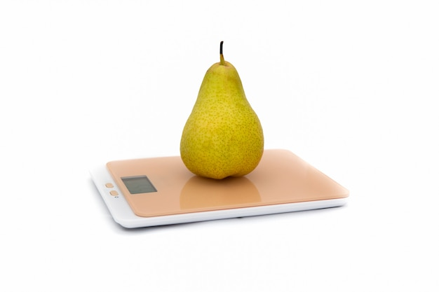 Зеленая груша на кухонные весы на белом.