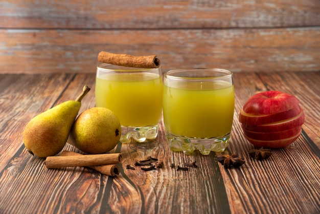 Green pear and red apple with a glass of juice