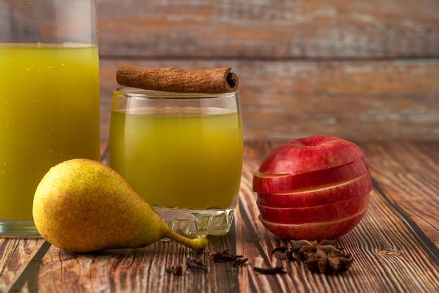 Pera verde e mela rossa con un bicchiere di succo