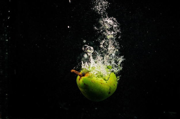 Green pear splashes water falling on black background