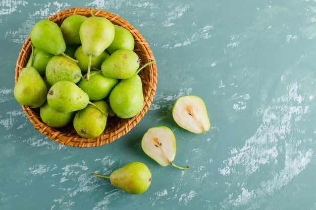 Green pears in a basket on a plaster surface