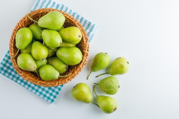 Зеленые груши в корзине на белизне и кухонном полотенце. плоская планировка