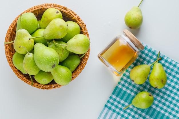 Зеленые груши в корзине с медом плоско лежат на белом и кухонном полотенце