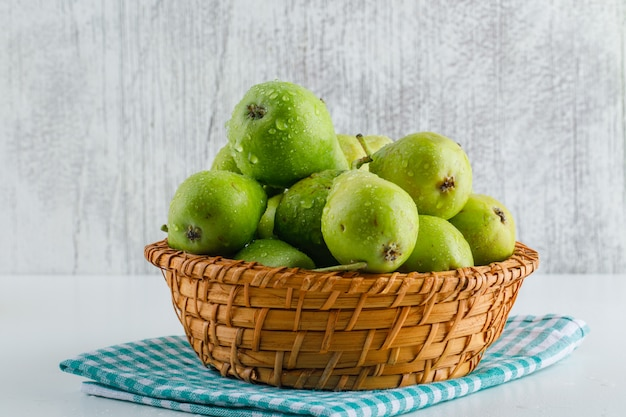 Green pears with kitchen towel in a basket on white and grungy.