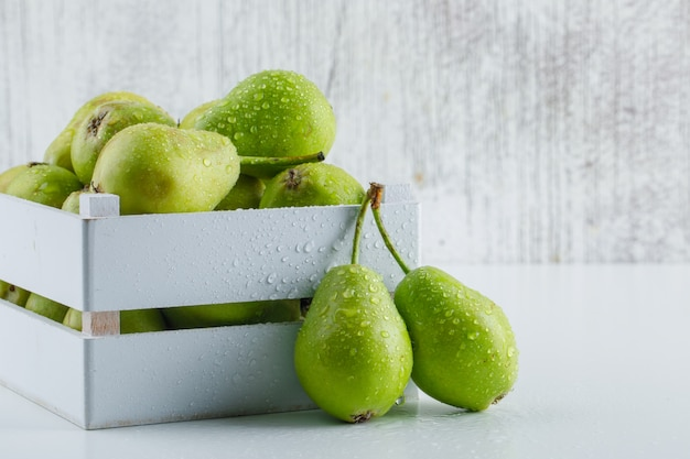 Green pears in a wooden box on white and grungy background, side view.