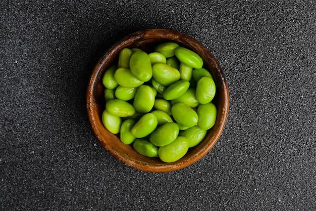 녹색 완두콩 근접 촬영입니다. 어두운 콘크리트 탁자 위에 있는 나무 그릇에 있는 녹색 콩
