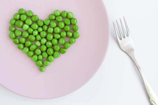 Green peas heart shaped, pink plate and a fork on white table. st. valentine's day concept